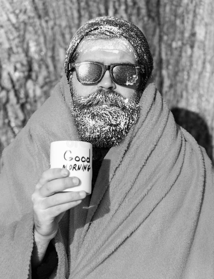 Uomo congelato, pantaloni a vita bassa barbuti, con la barba ed i baffi in occhiali da sole neri coperti di gelo bianco avvolto i fotografia stock