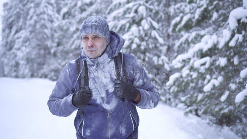 Uomo congelato ritratto con uno zaino, coperto di neve nella foresta di inverno fotografia stock libera da diritti