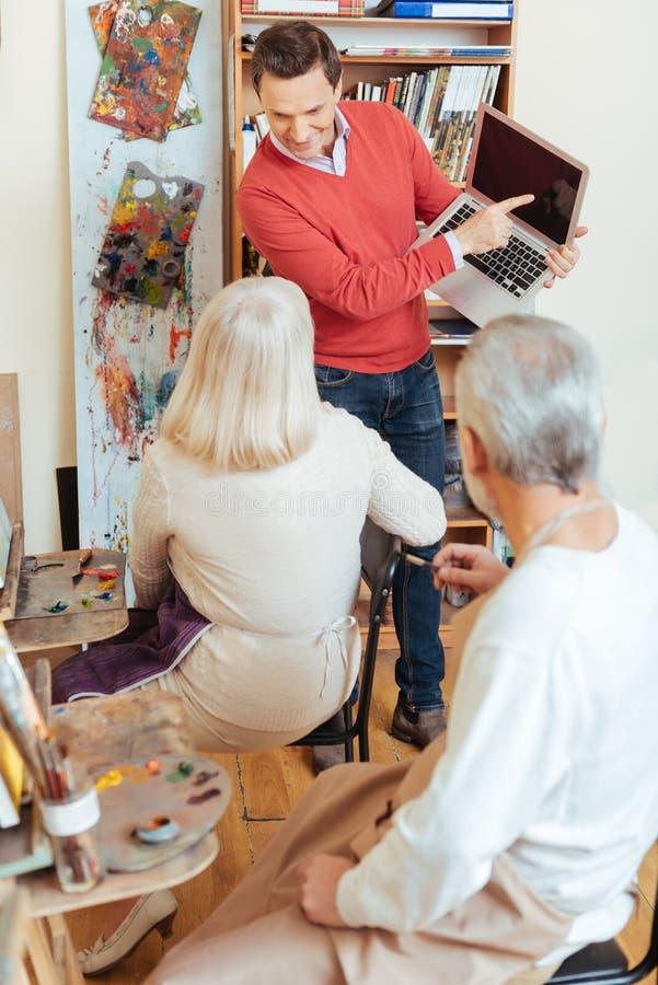 Uomo contentissimo che mostra computer portatile ai colleghi nello studio della pittura immagine stock