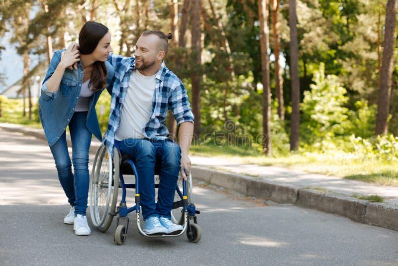 Uomo contentissimo positivo che si siede sulla sedia a rotelle fotografia stock libera da diritti
