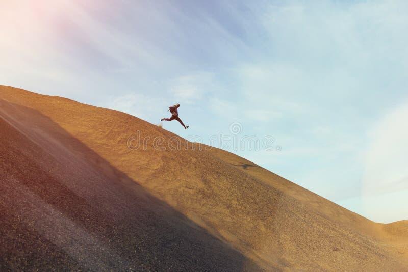 Uomo coraggioso con funzionamento ed il salto dello zaino su una duna immagine stock