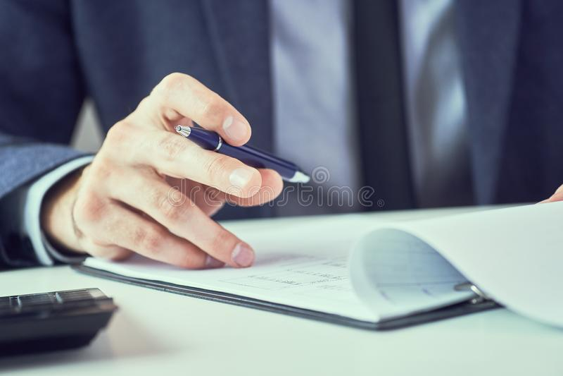 Uomo corporativo con la penna a disposizione che lavora nell'ufficio moderno, documento di firma di affari sullo scrittorio Fine  fotografia stock