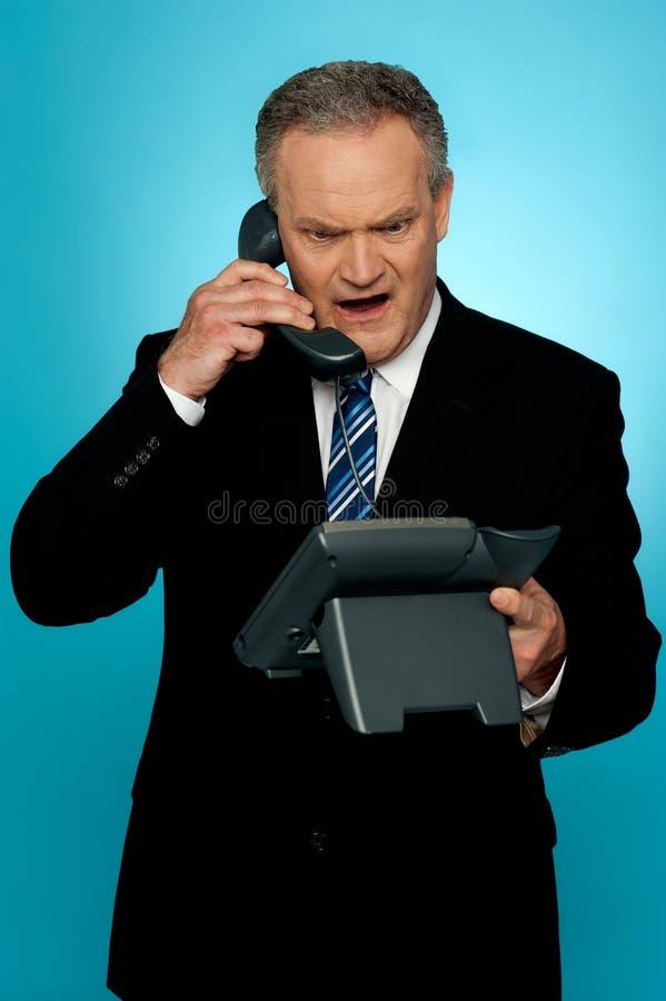 Uomo corporativo invecchiato arrabbiato che urla sul telefono fotografia stock