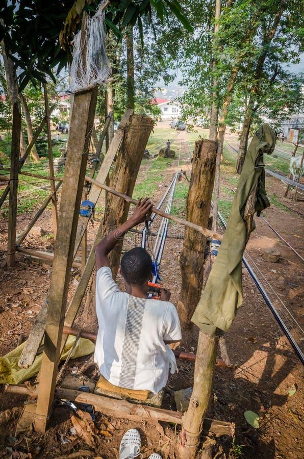 Uomo, Costa d'Avorio - gennaio 31,2014: Uomo africano non identificato che tesse il panno blu e bianco tradizionale di Yacouba al fotografie stock libere da diritti