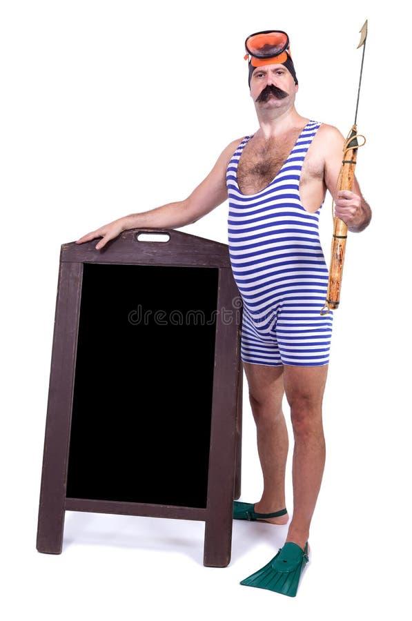 Uomo in costume da bagno che sta con l'arpone fotografia stock