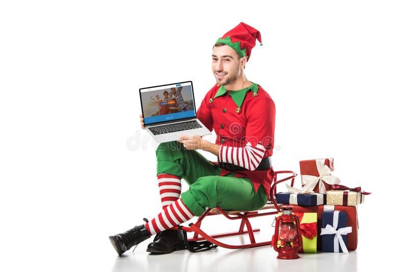 uomo in costume dell'elfo di natale che si siede sulla slitta e che giudica computer portatile con il sito Web couchsurfing sullo fotografia stock libera da diritti