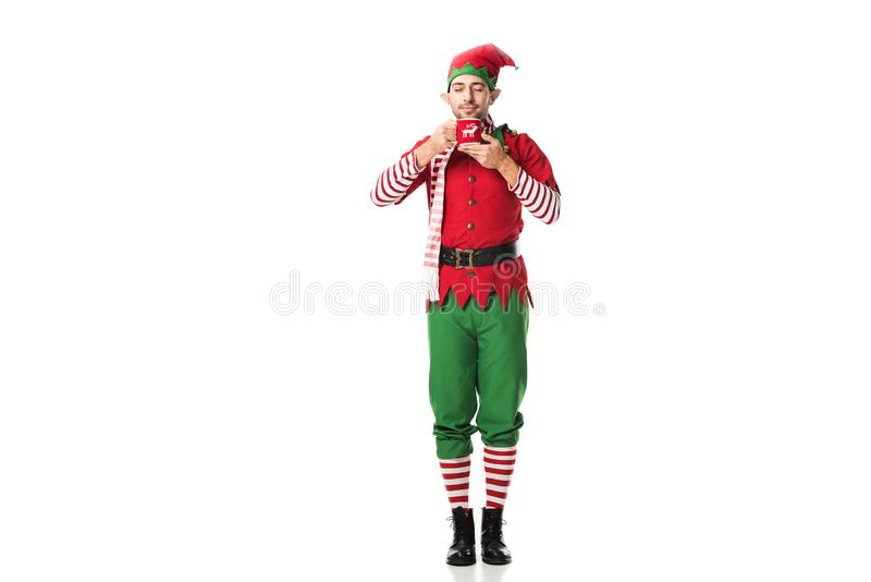 uomo in costume dell'elfo di natale con gli occhi chiusi tenendo tazza di tè ed inalando aroma isolato fotografia stock