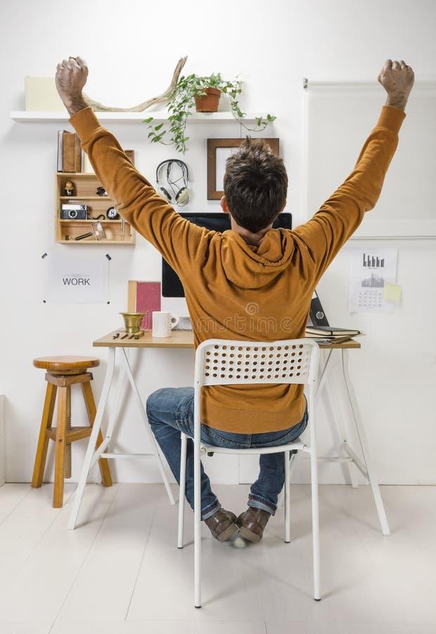 Uomo creativo moderno che celebra un successo su area di lavoro. fotografia stock libera da diritti