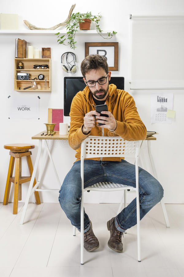 Uomo creativo moderno con lo smartphone su area di lavoro. fotografia stock libera da diritti