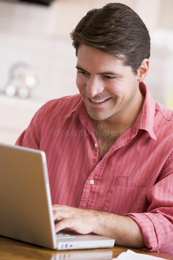 Uomo in cucina usando sorridere del computer portatile immagine stock libera da diritti