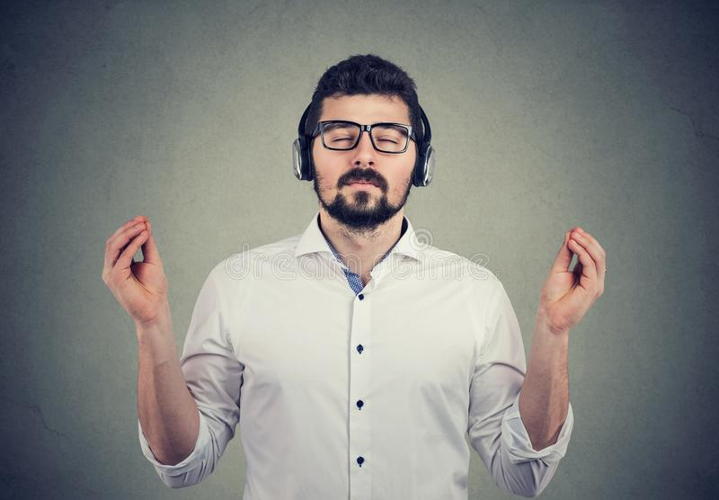 Uomo in cuffie con gli occhi chiusi che ascolta la musica e meditare fotografia stock
