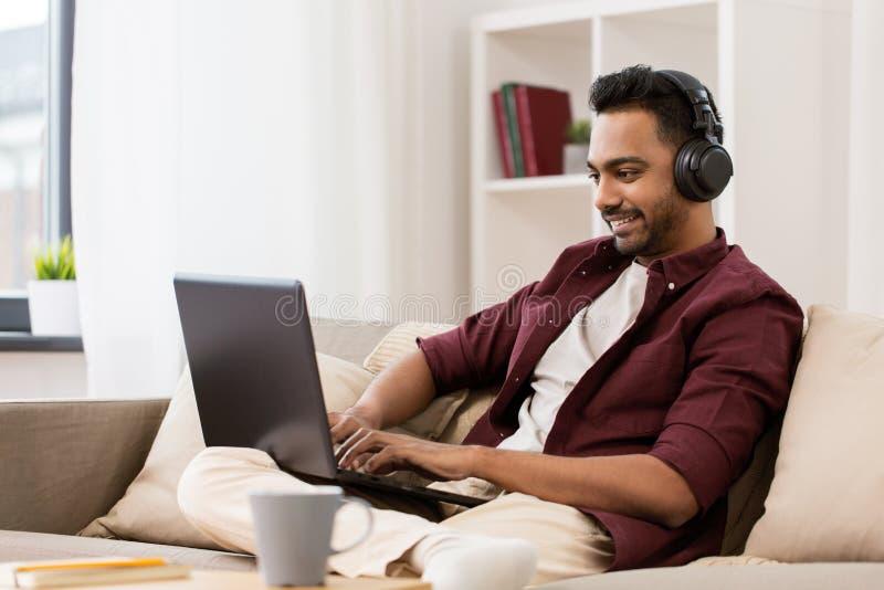 Uomo in cuffie con il computer portatile che ascolta la musica immagine stock