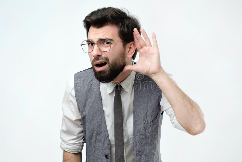 Uomo curioso o sordo che dispone mano sull'orecchio che chiede la parola qualcuno su o che ascolta le cattive notizie fotografie stock