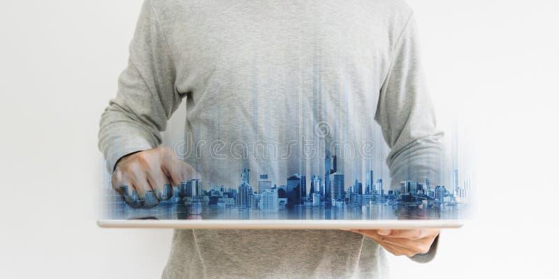 Uomo d'affari in abbigliamento casuale facendo uso della compressa digitale, con le costruzioni moderne futuristiche dell'ologram fotografia stock