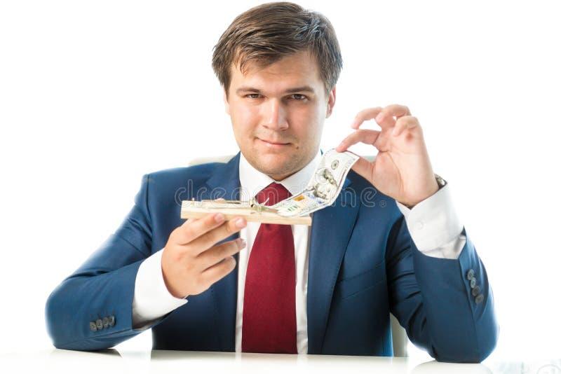 Uomo d'affari abile che prende banconota in dollari dalla trappola per topi fotografia stock