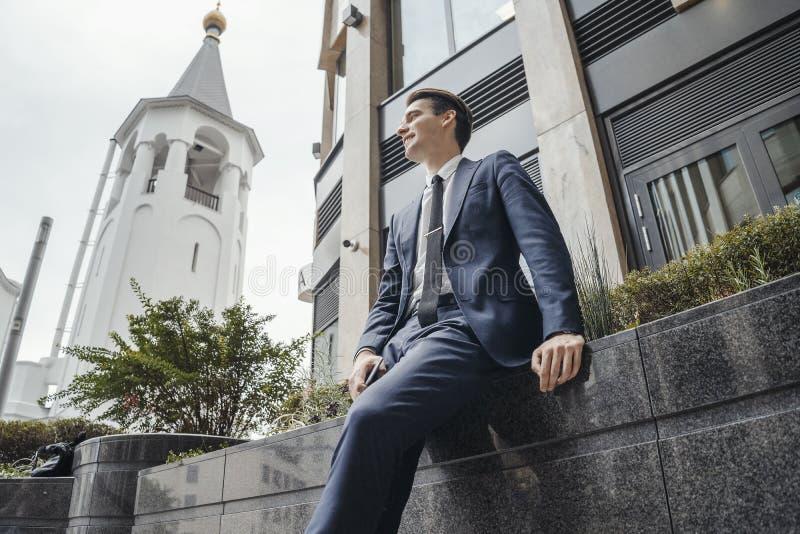 Uomo d'affari accanto al centro di affari alla città che aspetta una riunione fotografie stock libere da diritti