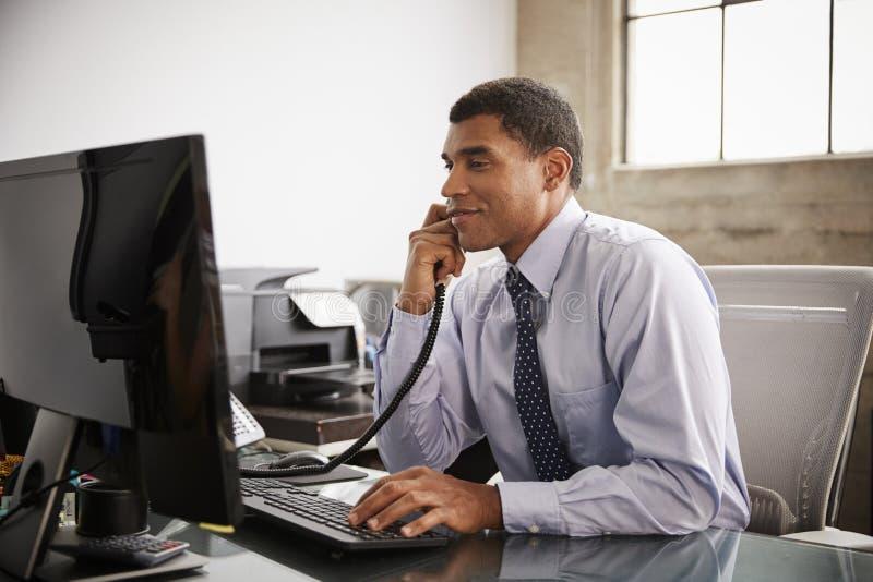 Uomo d'affari ad una scrivania facendo uso del telefono e del computer immagini stock