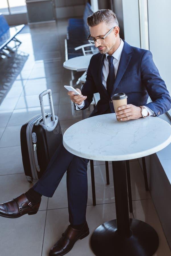 uomo d'affari adulto che per mezzo dello smartphone e bevendo caffè fotografia stock