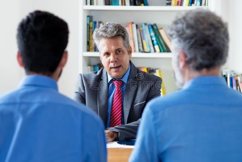 Uomo d'affari adulto maturo che parla con gli uomini d'affari fotografie stock