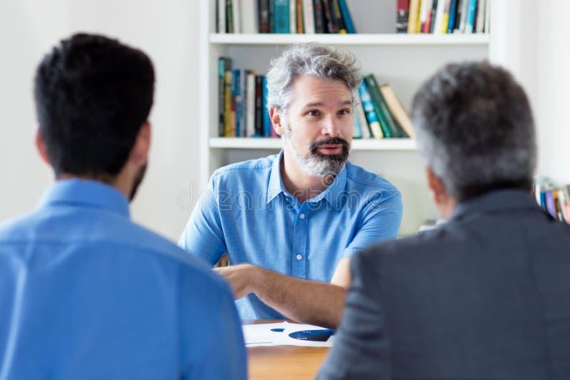 Uomo d'affari adulto maturo con la barba che parla con i colleghi fotografia stock libera da diritti