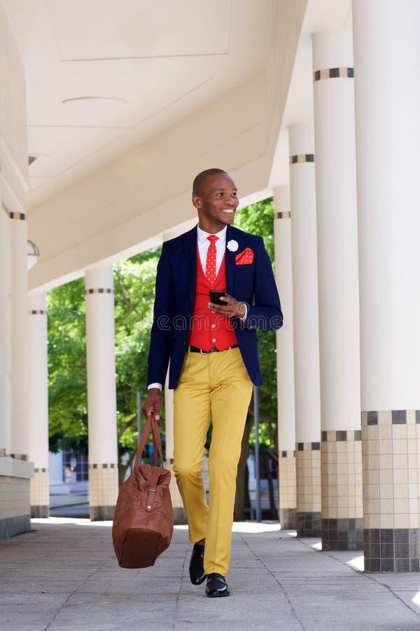Uomo d'affari africano bello che cammina con il telefono cellulare fotografia stock libera da diritti