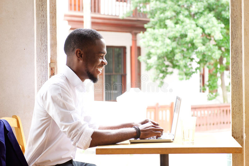 Uomo d'affari africano bello che sorride con il computer portatile immagini stock