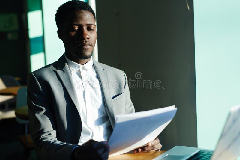 Uomo d'affari africano bello Working con le carte immagini stock libere da diritti