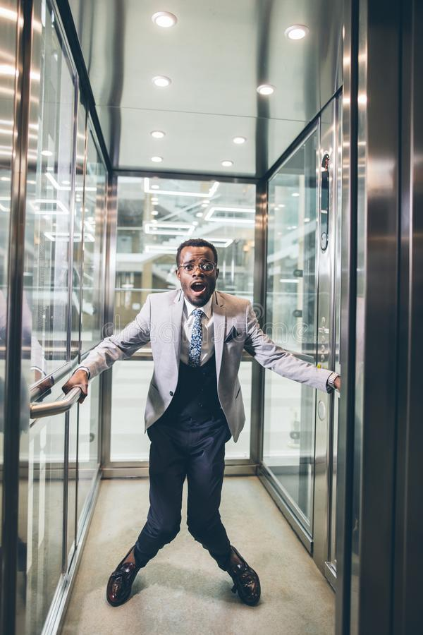 Uomo d'affari africano che grida in elevatore concetto di claustrofobia di timore immagine stock