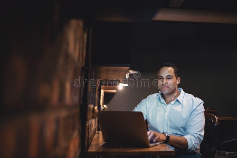 Uomo d'affari africano che lavora fuori orario nell'ufficio immagini stock libere da diritti