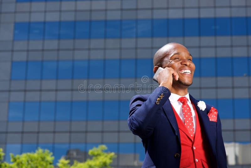Uomo d'affari africano che parla sul telefono cellulare e sulla risata fotografia stock