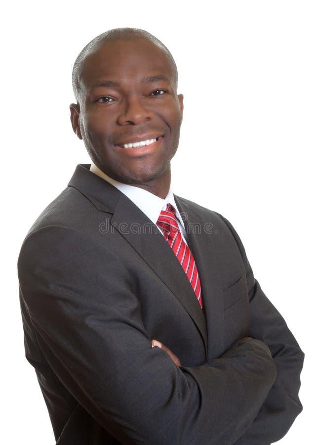 Uomo d'affari africano diritto con le armi attraversate immagini stock