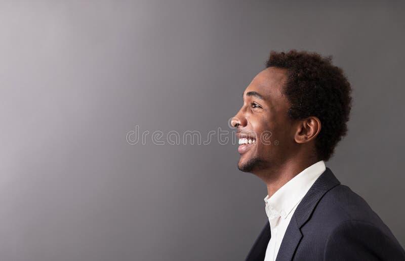 Uomo d'affari africano felice contro fondo grigio fotografie stock