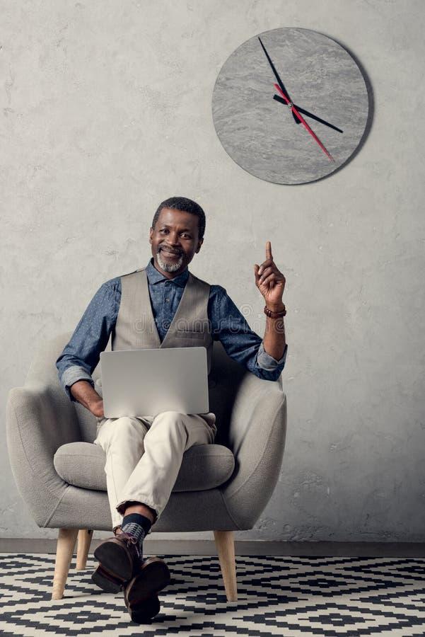 uomo d'affari afroamericano alla moda che indica su e che utilizza computer portatile nell'ufficio con l'orologio fotografia stock