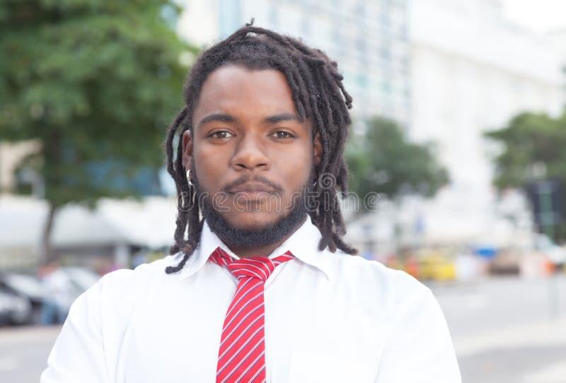 Uomo d'affari afroamericano astuto con i dreadlocks nella città fotografia stock