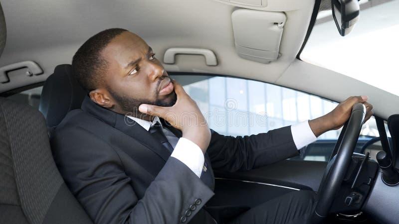 Uomo d'affari afroamericano bello che guarda in specchio di automobile, avendo dubbi fotografie stock