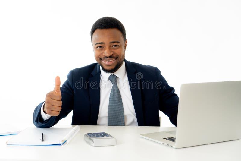 Uomo d'affari afroamericano bello felice attraente che lavora al computer portatile sullo scrittorio all'ufficio fotografie stock