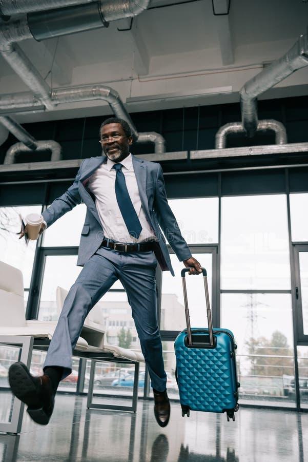 Uomo d'affari afroamericano che è in corsa per volo all'aeroporto fotografia stock