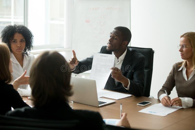 Uomo d'affari afroamericano che è in disaccordo con la clausola contrattuale a immagini stock