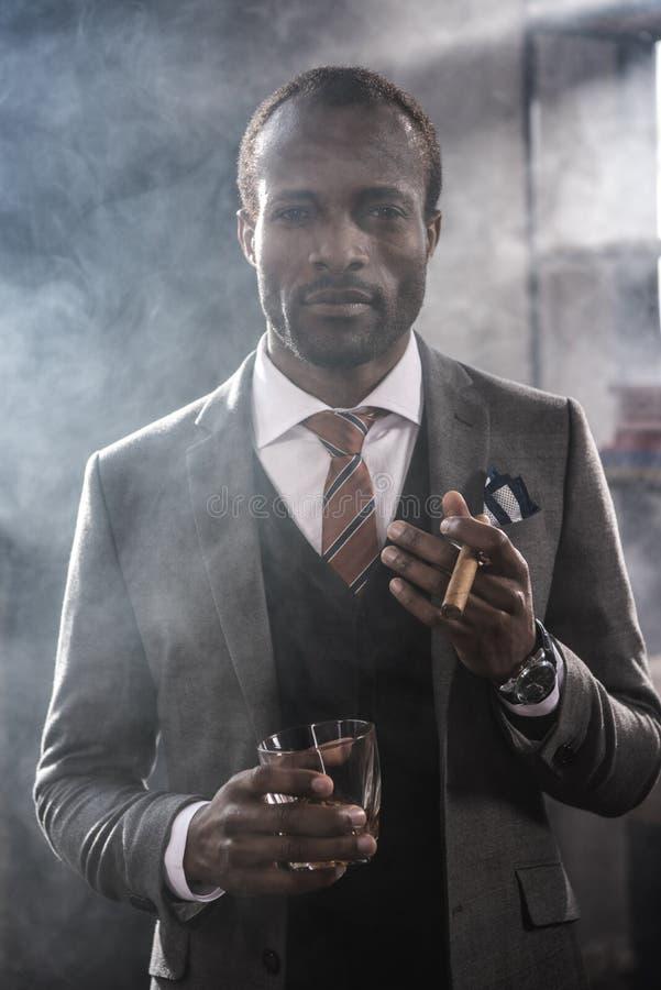 Uomo d'affari afroamericano che giudica di vetro con whiskey ed il sigaro di fumo fotografie stock