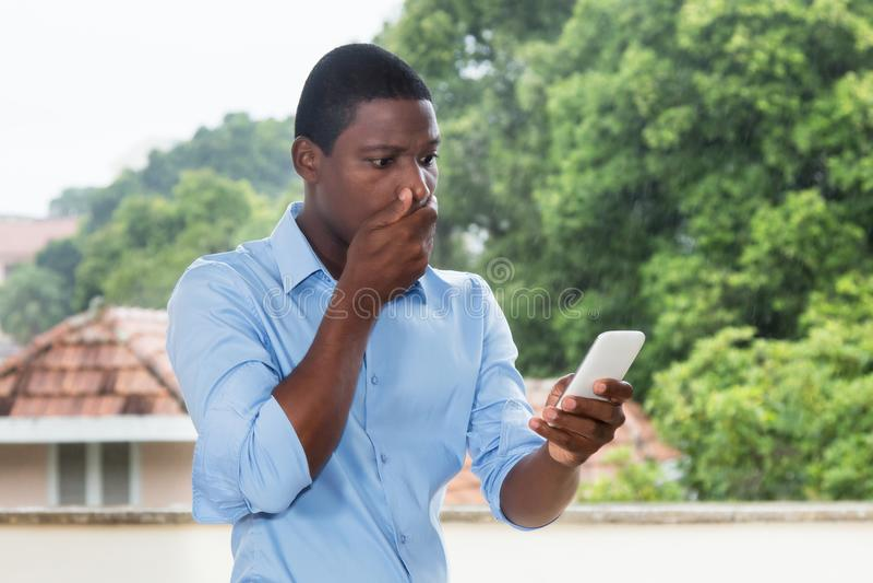 Uomo d'affari afroamericano che riceve messaggio di testo con cattivo nuovo fotografia stock libera da diritti