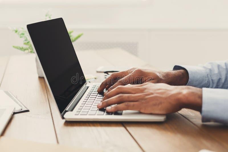 Uomo d'affari afroamericano che scrive sul computer portatile fotografia stock