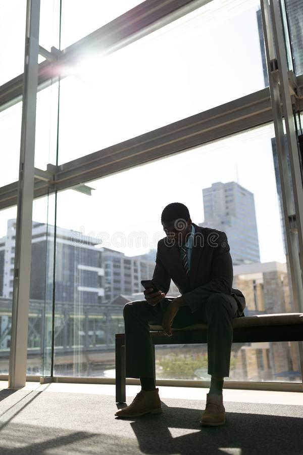 Uomo d'affari afroamericano che si siede sul banco e che utilizza telefono cellulare nell'ufficio fotografie stock