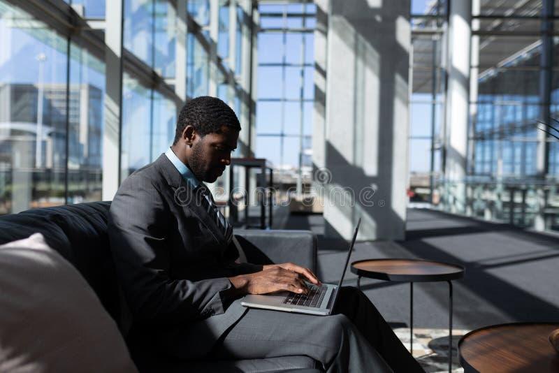 Uomo d'affari afroamericano che si siede sul sofà e che utilizza computer portatile nell'ufficio moderno fotografia stock