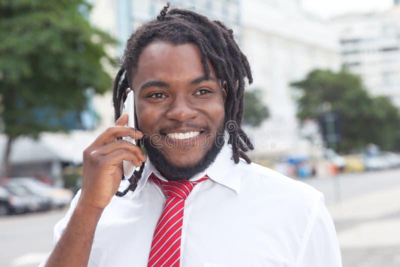 Uomo d'affari afroamericano con i dreadlocks al telefono nella città fotografia stock