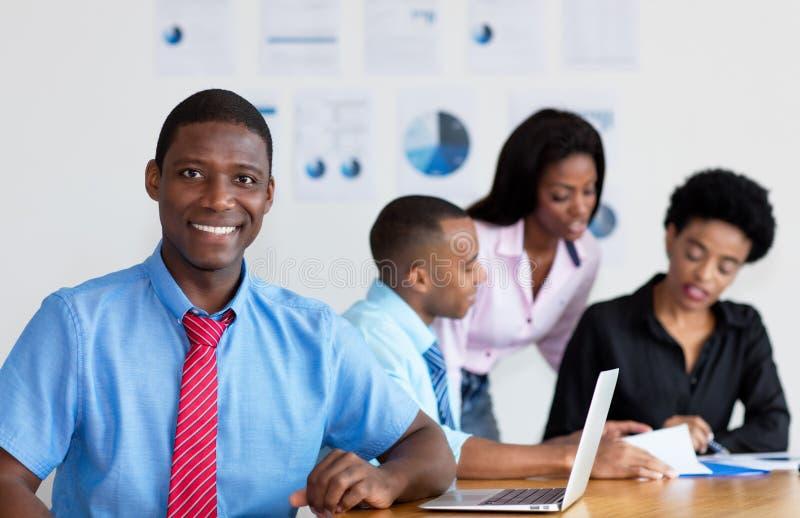 Uomo d'affari afroamericano con il gruppo di affari all'ufficio fotografia stock libera da diritti
