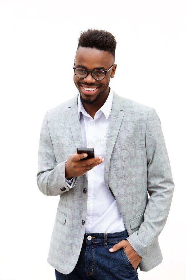 Uomo d'affari afroamericano con il telefono cellulare contro fondo bianco immagine stock libera da diritti