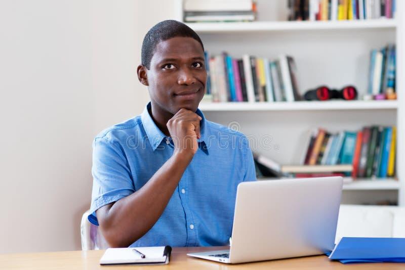 Uomo d'affari afroamericano di pensiero con il computer portatile fotografie stock