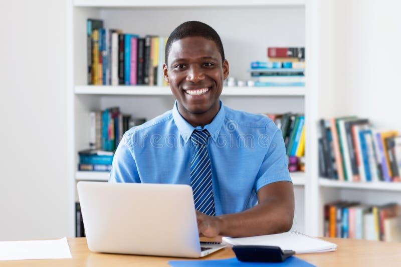 Uomo d'affari afroamericano di risata con la cravatta al computer immagine stock libera da diritti