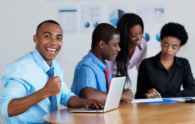 Uomo d'affari afroamericano felice con il gruppo di affari all'ufficio fotografia stock libera da diritti