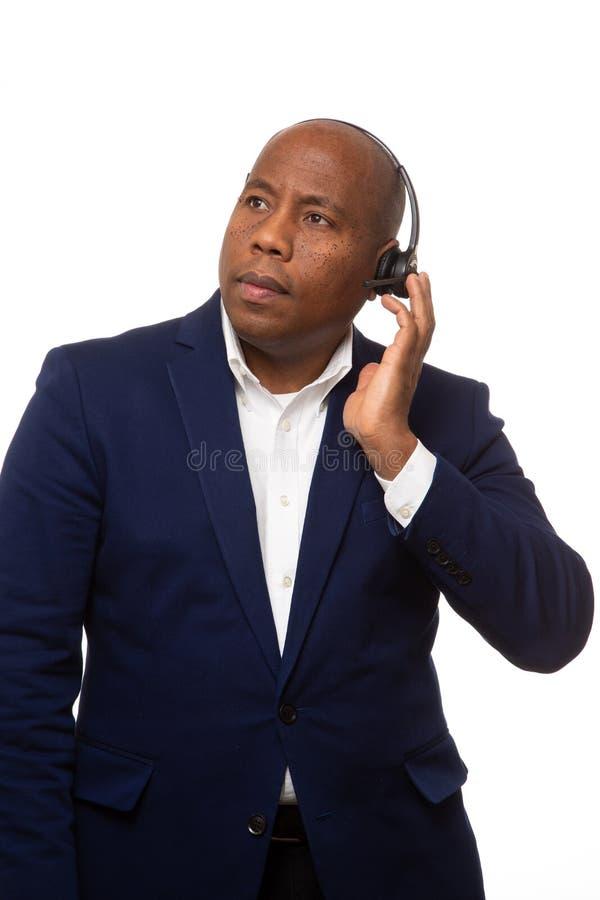 Uomo d'affari afroamericano Listens Through Headset immagini stock libere da diritti